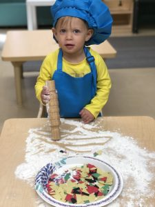 A child play with flour and pasta at Temple Shalom.