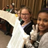 Temple Shalom youth and adults unrolling Torah scroll for Simcha Torah in Social Hall